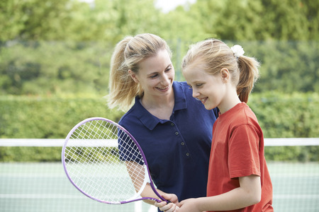ni�os estudiando: Mujer Tennis Coach Dar Lecci�n Para Chica Foto de archivo