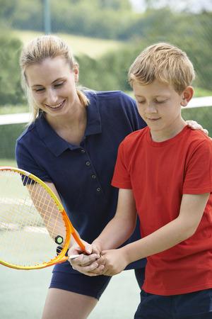 tennis racket: Female Tennis Coach Giving Lesson To Boy