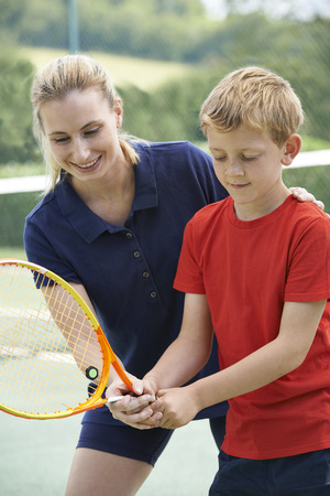 jugando tenis: Mujer Tennis Coach Dar Lección Para Boy
