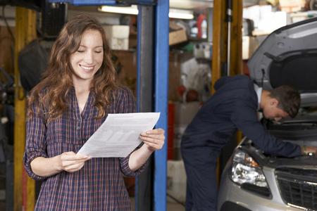 Vrouwelijke klant in Auto Repair Shop tevreden met Bill GARAGEGEREEDSCHAP Stockfoto