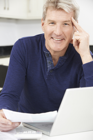 computer security: Smiling Mature Man Reviewing Domestic Finances Stock Photo