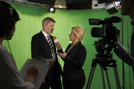 Vrouwelijke presentator interviewen In Televisie Studio Met Crew In Voorgrond Stockfoto