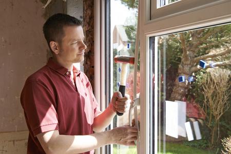 Construction Worker Installing New Windows In House Standard-Bild