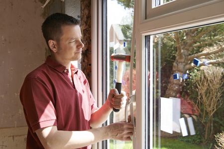 install: Construction Worker Installing New Windows In House Stock Photo