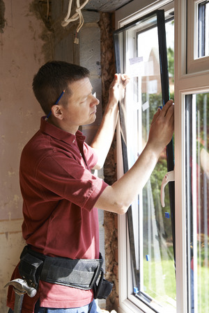 contractor: Construction Worker Installing New Windows In House Stock Photo