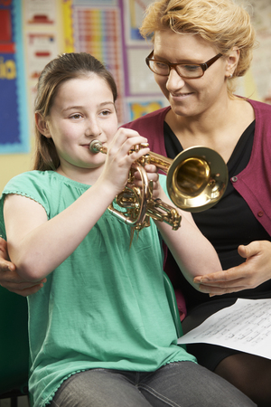 school class: Teacher Helping Pupil To Play Trumpet In Music Lesson Stock Photo