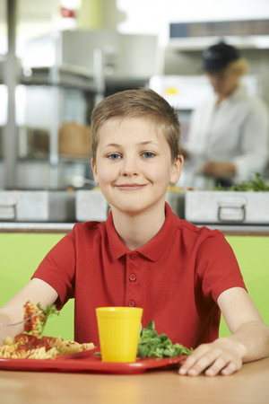 cafeteria tray: Male Pupil Sitting At Table In School Cafeteria Eating Lunch Stock Photo