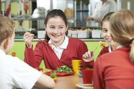 uniforme escolar: Grupo de alumnos sentado a la mesa en la cafetería de la escuela que come el almuerzo