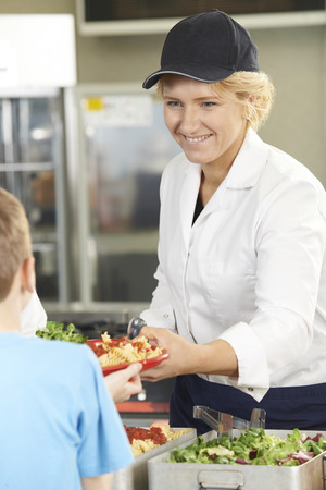 school uniforms: Pupil In School Cafeteria Being Served Lunch By Dinner Lady
