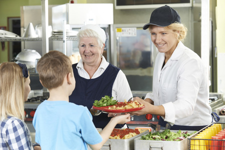 almuerzo: Los alumnos en cafetería de escuela Estar almuerzo servido por las señoras de la cena