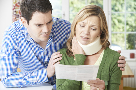 Couple Reading Letter In Respect Of Wifes Neck Injury