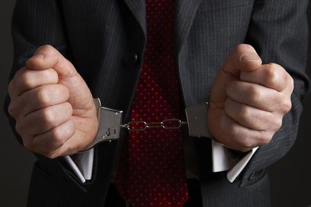 restraining: Businessman Wearing Handcuffs Illustrating Corporate Crime Stock Photo