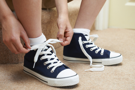 Boy Sitting On Stairs Tying Shoelaces Stock Photo