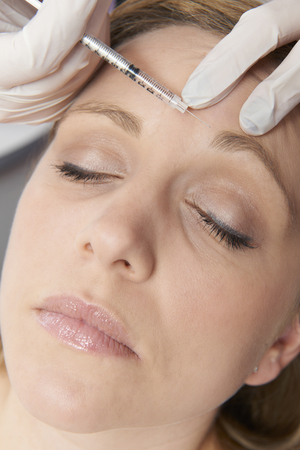 the ageing process: Woman Having Botox Injection In Forehead