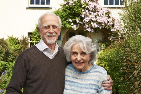 cottage: Senior Couple Standing Outside Pretty Cottage