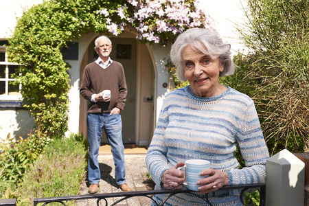 cottage garden: Senior Couple Standing In Cottage Garden With Coffee Cups