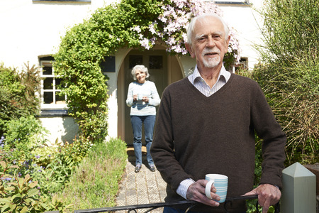 cottage garden: Senior Couple Standing In Cottage Garden Holding Coffee Cup Stock Photo