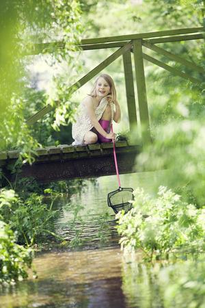 redes de pesca: Chica joven que coge pescado con red desde el puente de madera