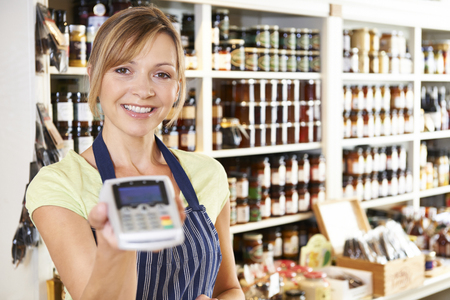 credit card: Asistente de Ventas en almacén de la comida con la máquina de tarjeta de crédito