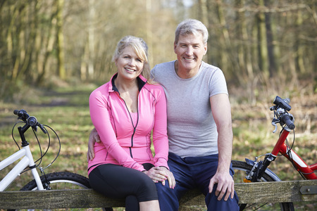 middle aged women: Mature Couple On Cycle Ride In Countryside Together
