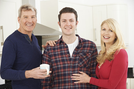 mom and dad: Portrait Of Family With Adult Son At Home Stock Photo