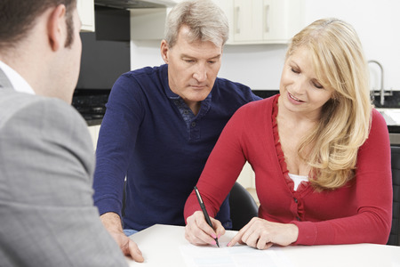 pensions: Mature Couple With Financial Advisor Signing Document At Home
