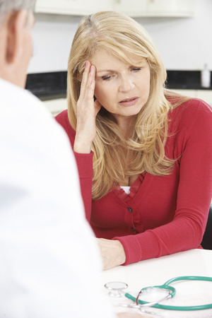 middle age women: Worried Mature Woman Meeting With Doctor In Surgery