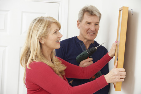 hanging woman: Mature Couple Drilling Wall To Hang Picture Frame