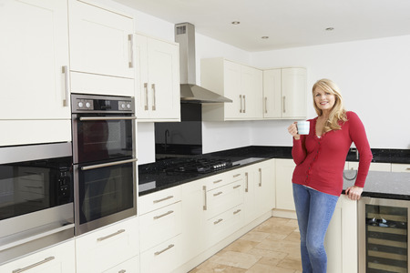 fitted: Mature Woman Standing In New Luxury Fitted Kitchen