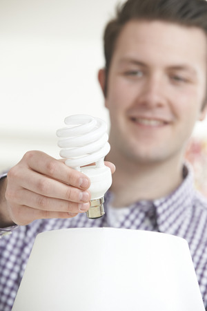 light green: Man Putting Low Energy Lightbulb Into Lamp At Home Stock Photo