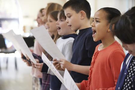 kinderen: Groep schoolkinderen zingen in koor Together Stockfoto