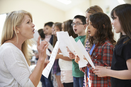 Children In Singing Group Being Encouraged By Teacher