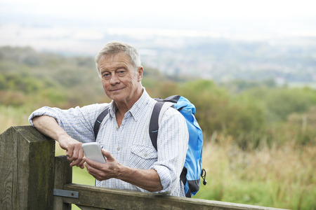 global retirement: Senior Man Checking Location With Mobile Phone On Hike
