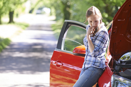 woman driving car: Worried Female Motorist Standing Next To Broken Down Car Stock Photo