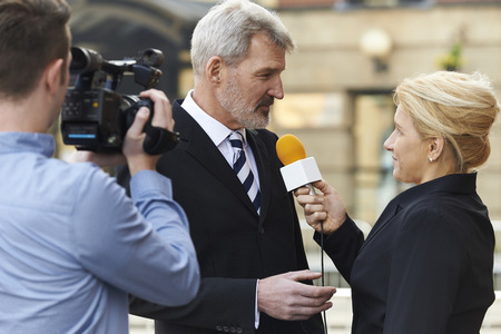 politics: Female Journalist With Microphone Interviewing Businessman Stock Photo
