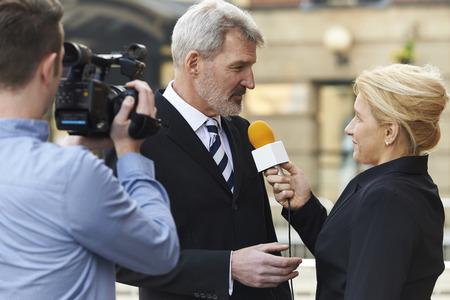 reportero: Periodista Mujer con el micr�fono Empresario Entrevistar Foto de archivo