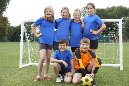 educacion fisica: Muchachos y muchachas en equipo de fútbol de la Escuela Primaria