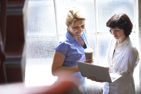 informal: Two Businesswomen Having Informal Meeting In Office