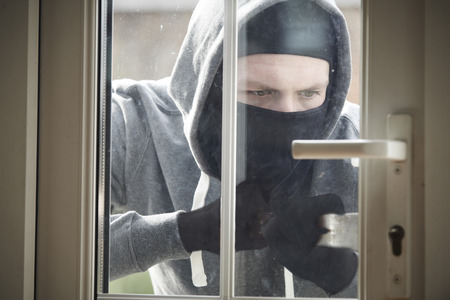 burglar: Burglar Breaking Into House By Forcing Door With Crowbar Stock Photo