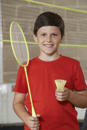 school gym: Portrait Of Boy In School Gym Playing Badminton Stock Photo