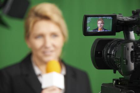 Female Journalist Presenting Report In Television Studio Stock Photo