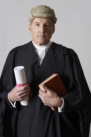 slander: Portrait Of Male Lawyer Holding Brief And Book Stock Photo