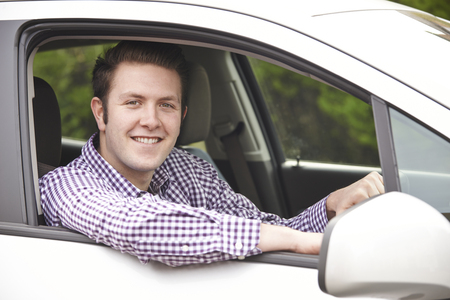 looking out: Portrait Of Young Male Driver Looking Out Of Car Window