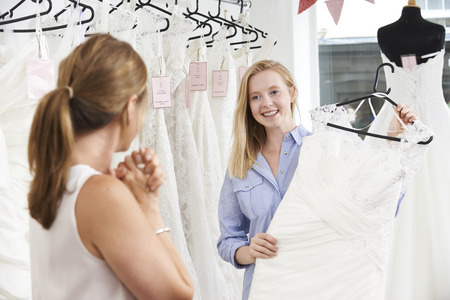 woman dress: Mother Helping Daughter To Choose Dress In Bridal Store Stock Photo