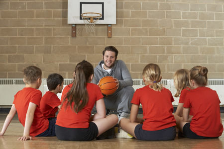 junior high: Coach Giving Team Talk To Elementary School Basketball Team