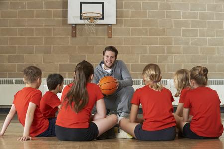 Coach Giving Teams im Gespräch mit Elementary School Basketball-Team