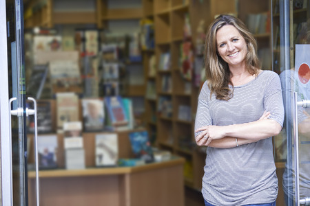 business owner: Portrait Of Female Bookshop Owner Outside Store Stock Photo