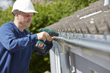 hard worker: Workman Replacing Guttering On Exterior Of House