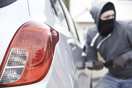 into: Masked Man Breaking Into Car With Crowbar Stock Photo