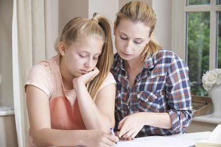 Female Home Tutor Helping Girl With Studies